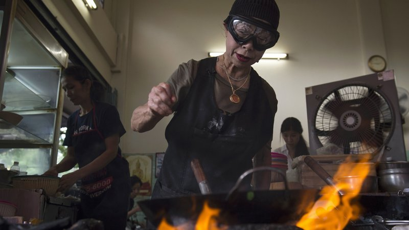 Chef Jay Fai wears a wool cap and safety goggles to ward off the heat from the charcoal fires in the alley where she cooks all of her restaurant's meals.