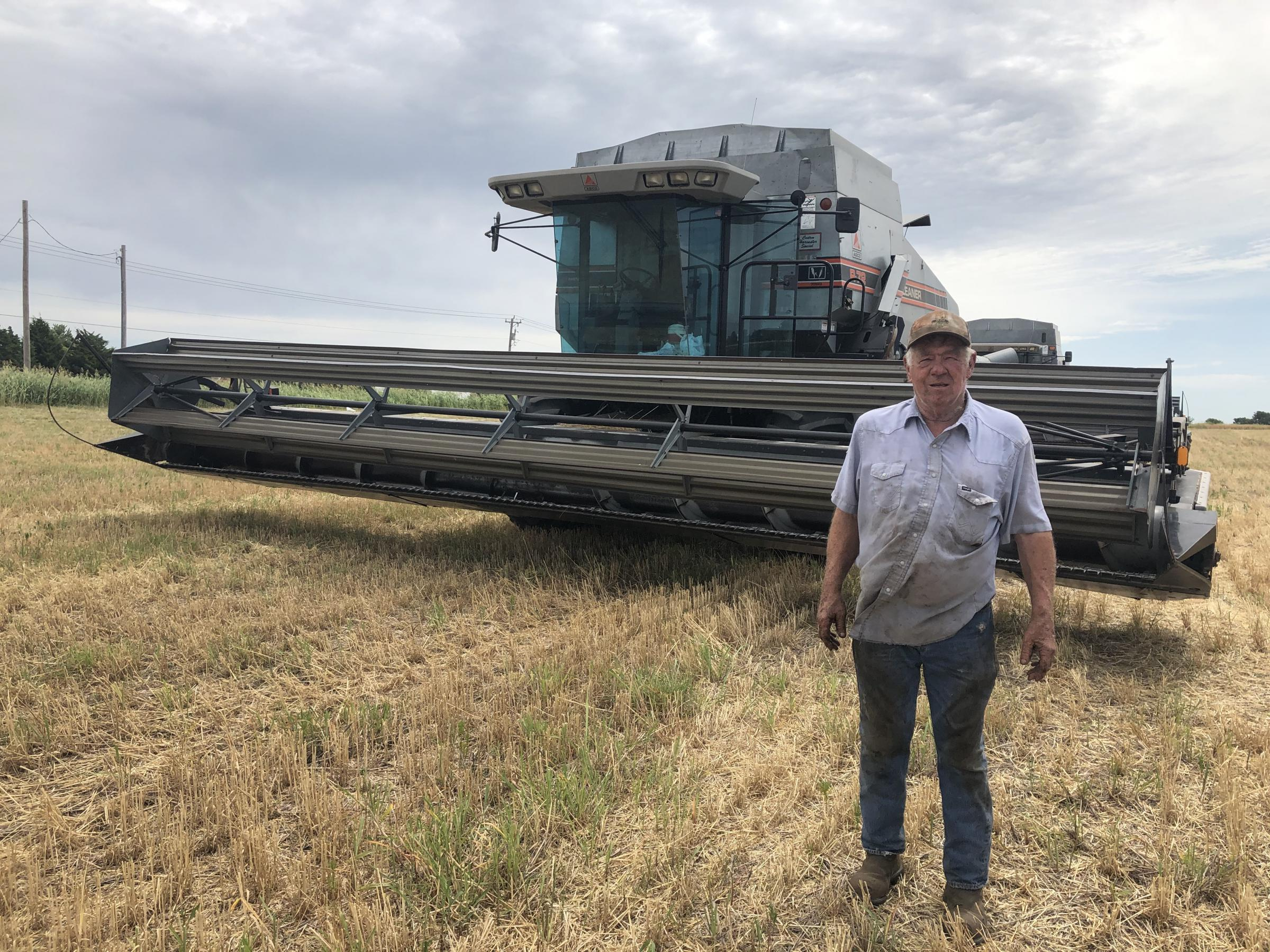 John Blair standing in front of a wheat combine in a wheat field.