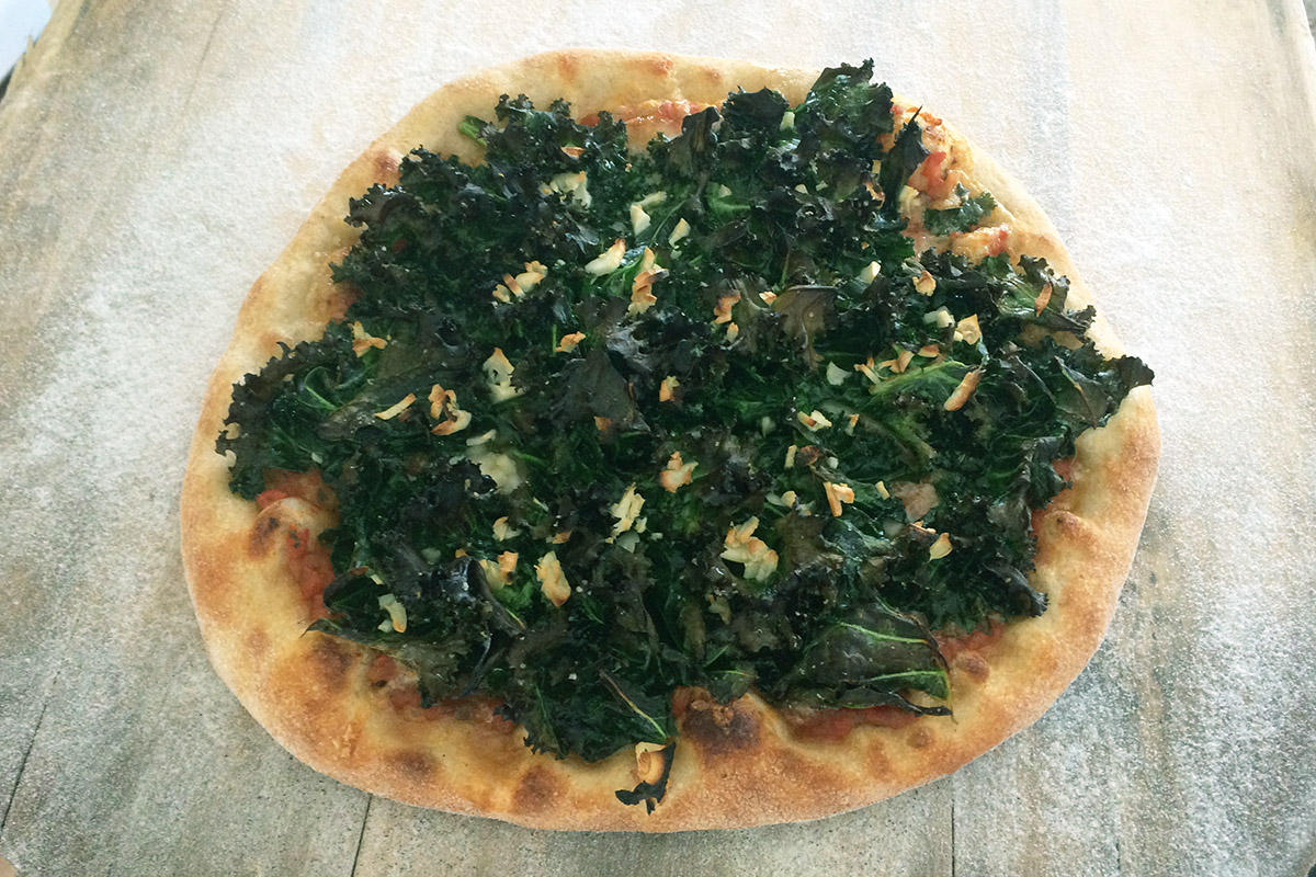 A small pizza piled with dark green kale