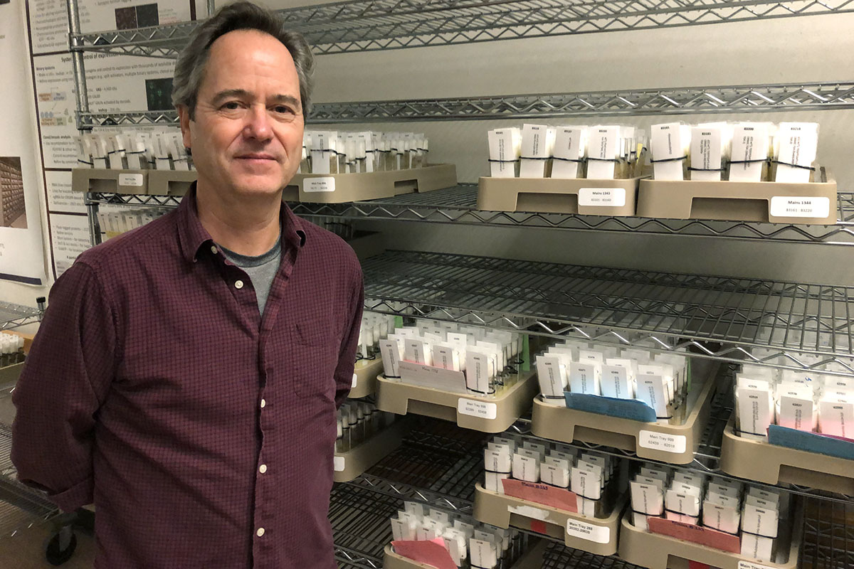 Kevin Cook standing in front of a rack full of trays of labled vials.