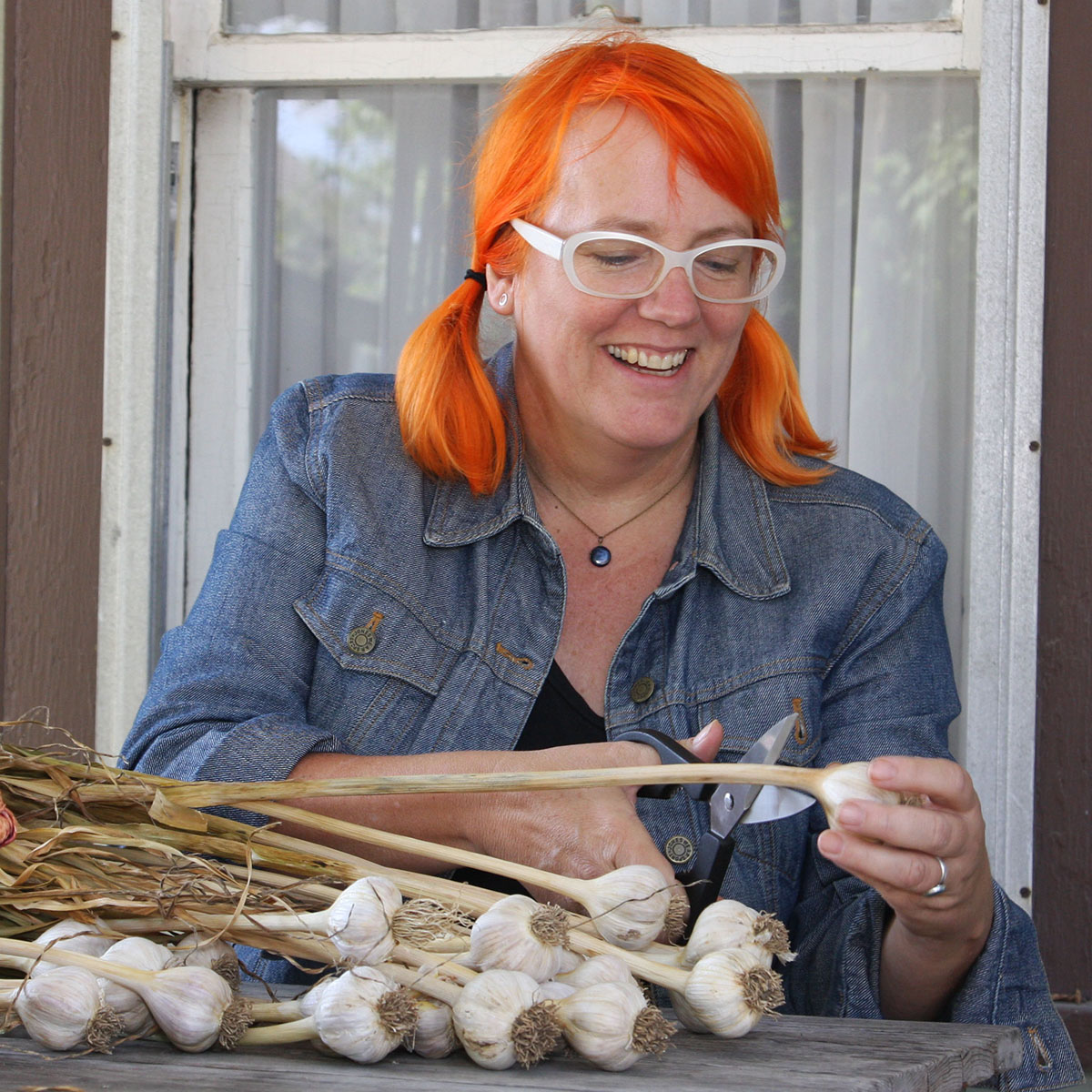 Kayte Young smiling while cutting a garlic stock, stitting at a table outdoors
