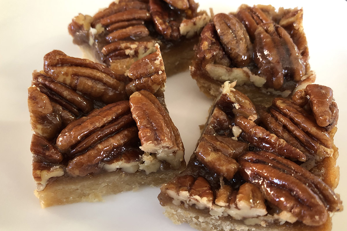 Four pecan bars arranged on a white plate.