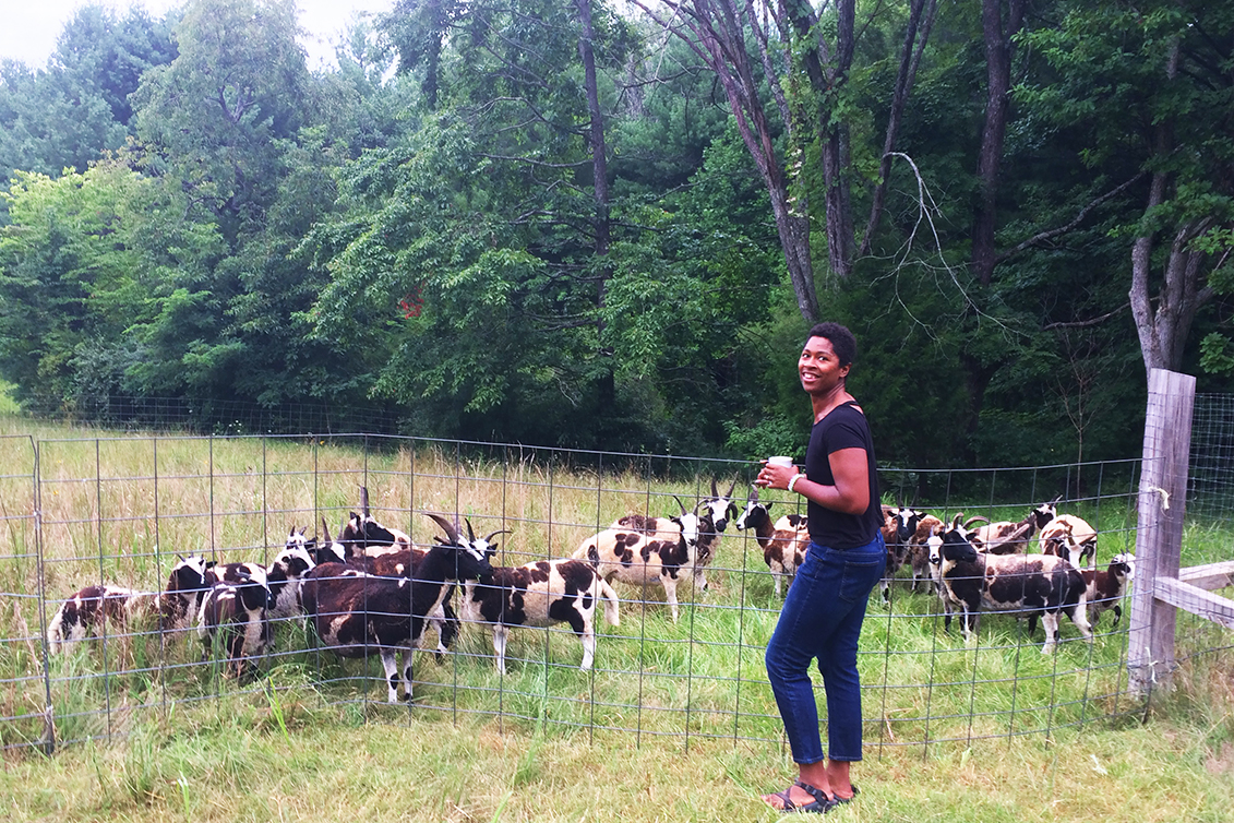 A black woman holding a coffee cup standing next to a wire fence with a flock of small sheep with large horns and multi colored pelts.