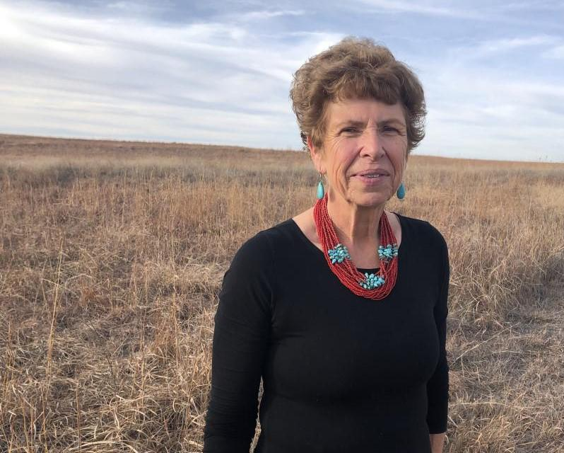 Mary Chris Barth standing in a field of brown grass, with a flat, uninterrupted horizon and gray blue sky
