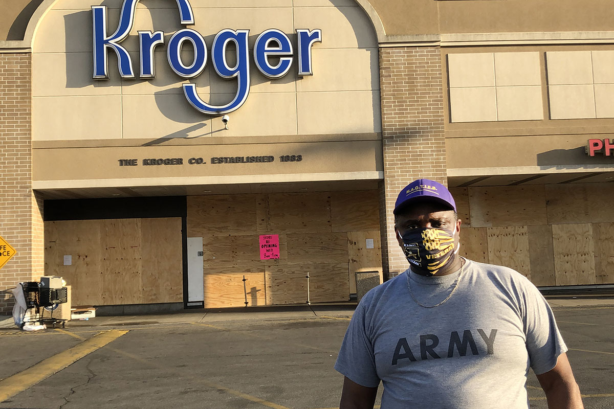 MeShorn Daniels with face mask and Army shirt, in ball cap looking at camera standing in parking lot of boarded-up Kroger.
