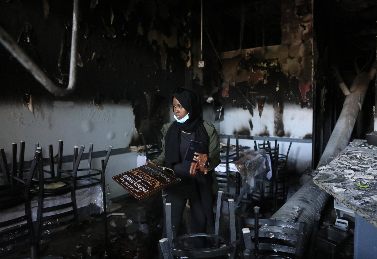 Saida Hassan in a black head scarf stands with a phone in one hand, a restaurant sign in the other, in burned out seating area of a restaurant.