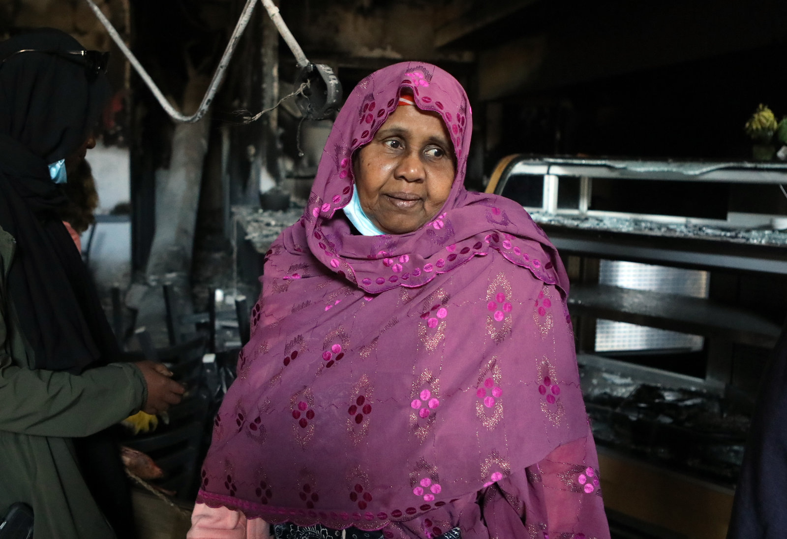 Safia Munye in a purple head scarf stands in front of burned restaurant equipment.