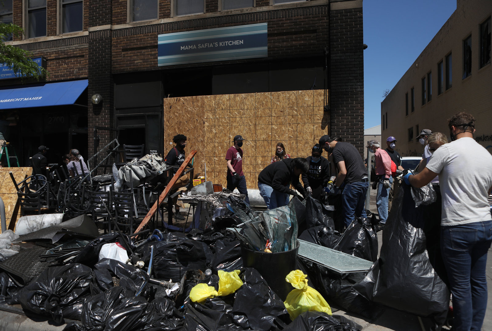 A large pile of full plastic trash bags in front of boarded up buildings, with people working in face masks.