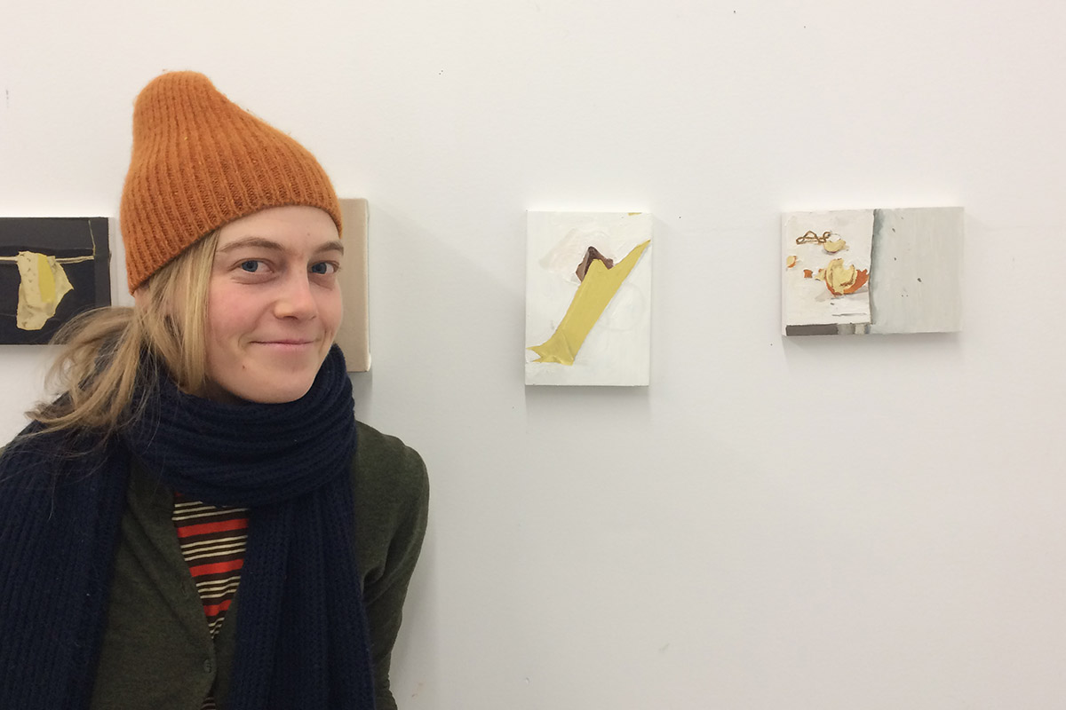 Young woman in winter hat and scarf standing in front of small paintings on a white wall.