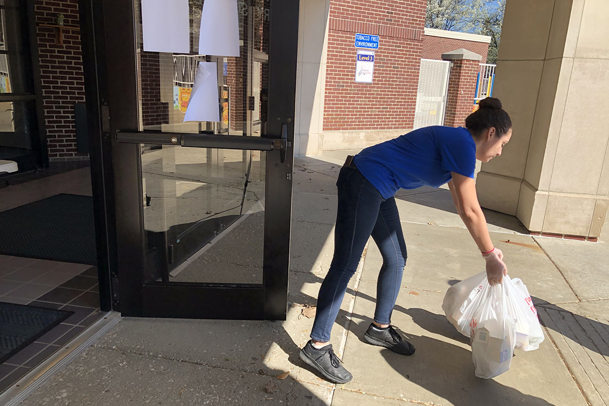 A young woman in a blue teeshirt places full white plastic grocery bags on the concrete outside of a school entrance