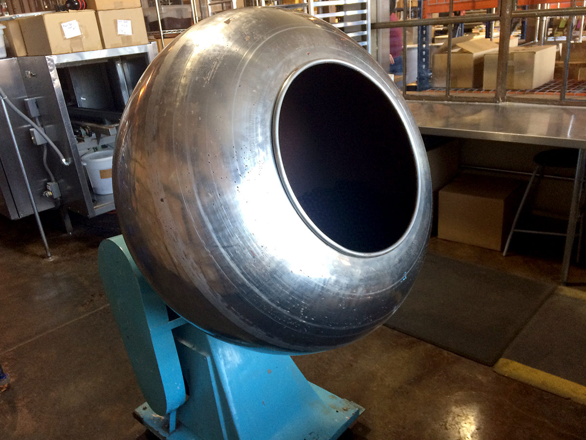 A big metal machine with a round steel barrel and a light blue base