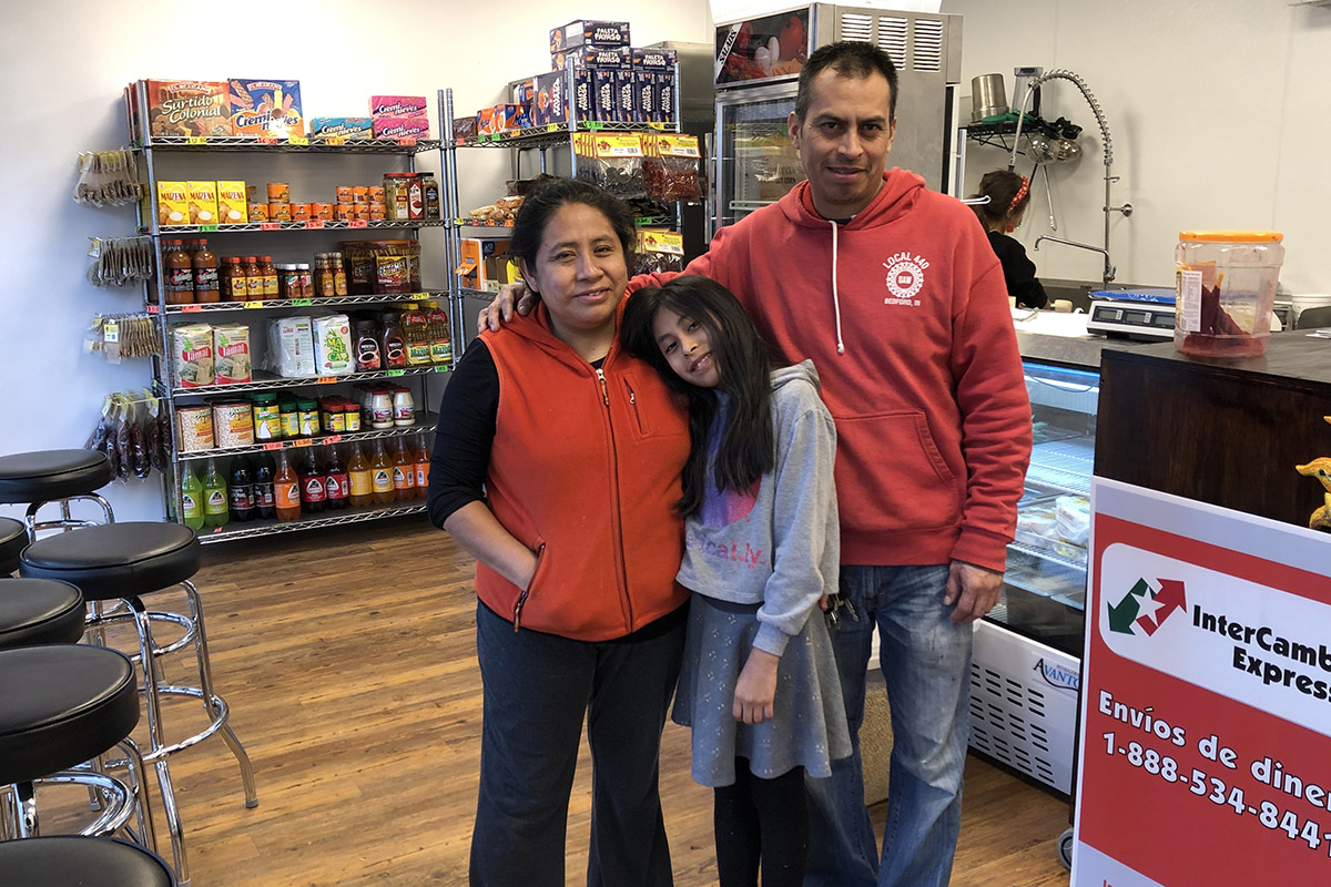 Pilar Gonzales with her husband and daughter standing in a small store with merchandise and barstools n background
