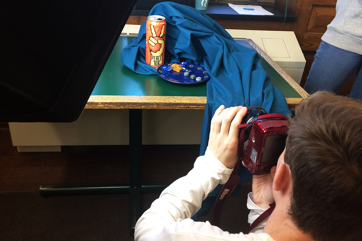 Student photographing and arrangement of a tea can and candy with a teal cloth on a table.  A lighting device is in view.