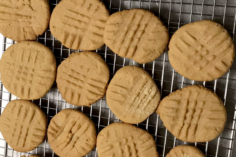 Peanutbutter cookies, with fork marks, on a cooling rack.