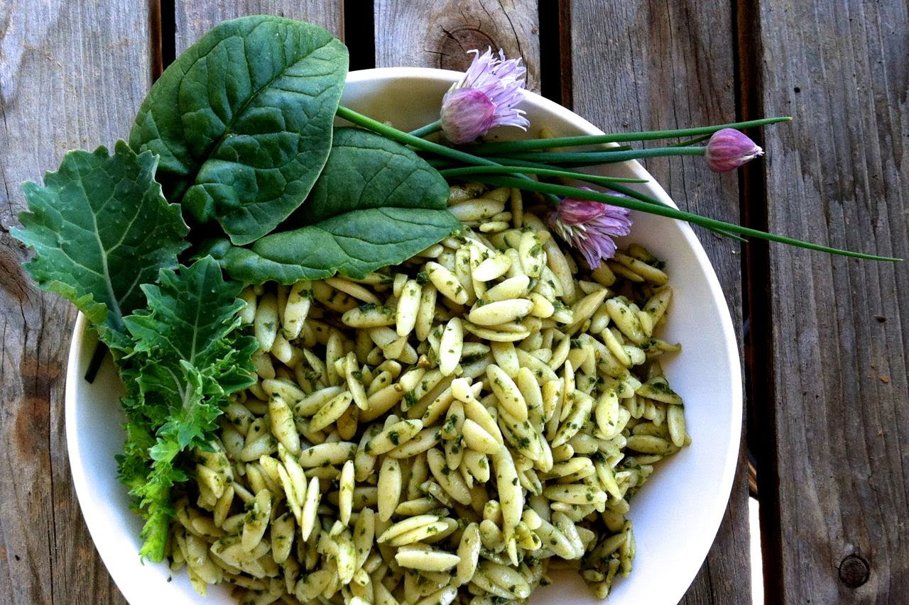 Pesto on orzo pasta with chive blossom, spinach and baby kale garnish--in a white bowl.