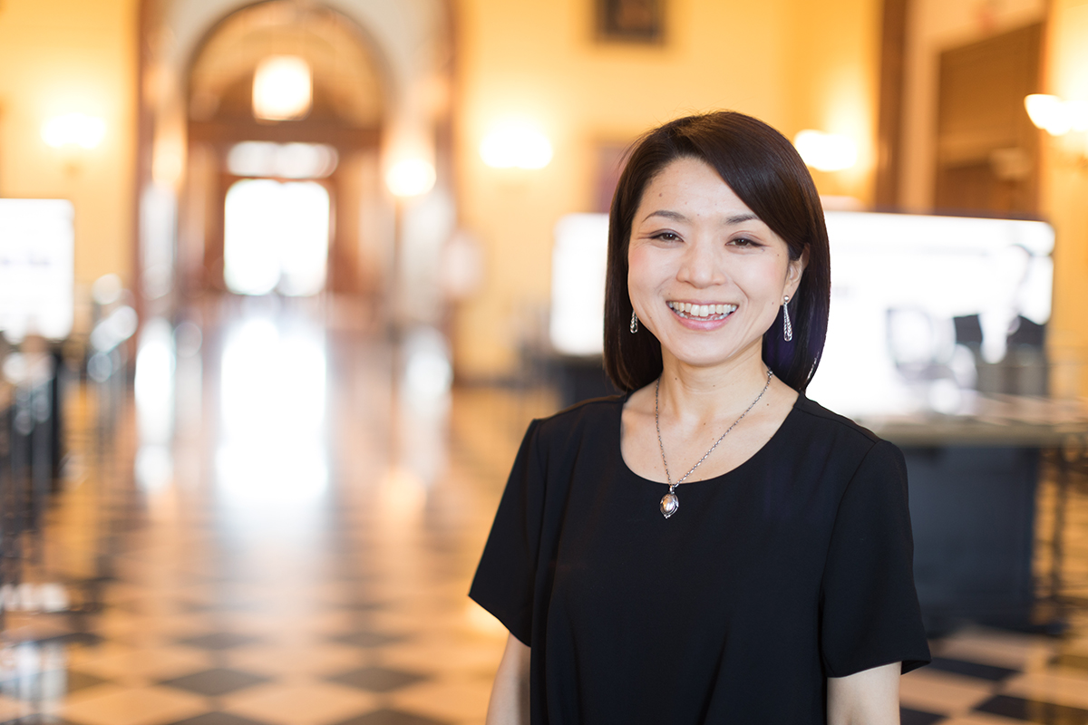 Portrait of Ai Hisano, smiling looking at camera, standing it a large hall