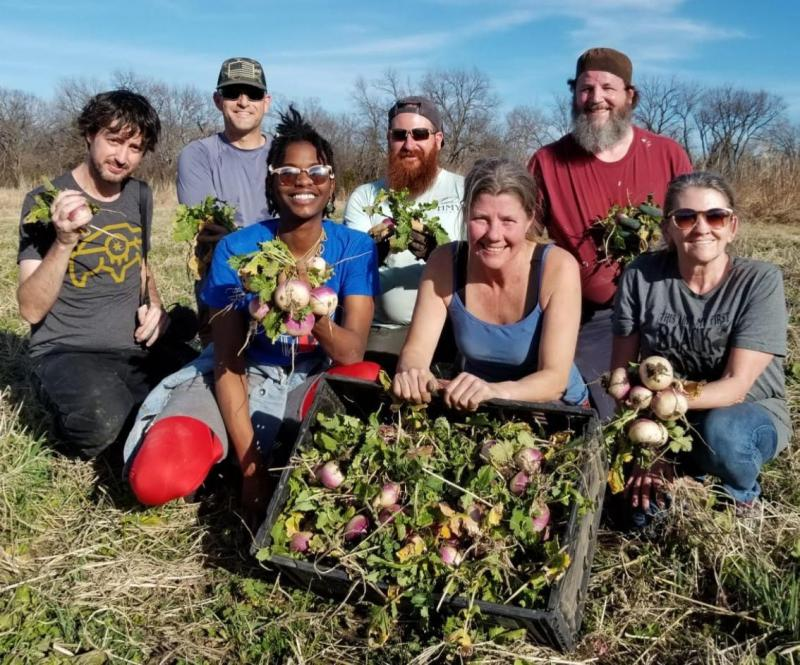 A group of 7 people, outdoors, holding bunches of turnips and presenting a crate full of turnips as they look towards the camera smiling.