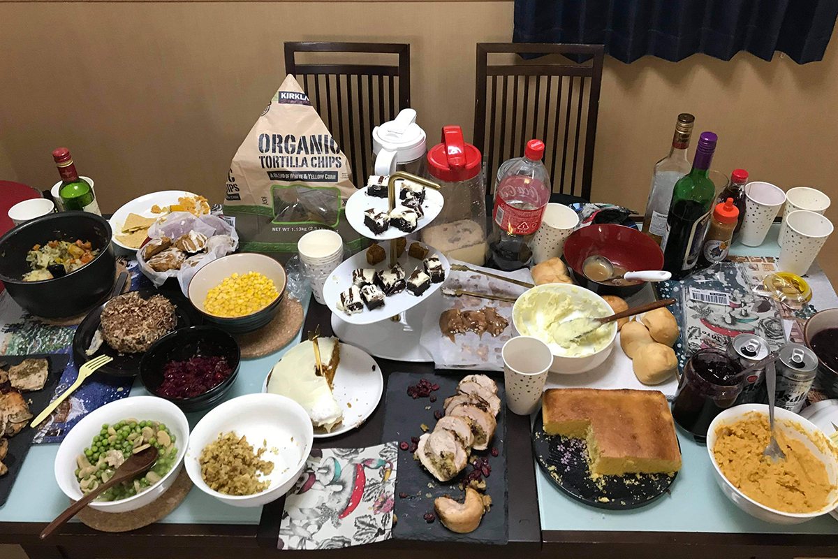 A table crowded with many different dishes of food and drink, partially consumed