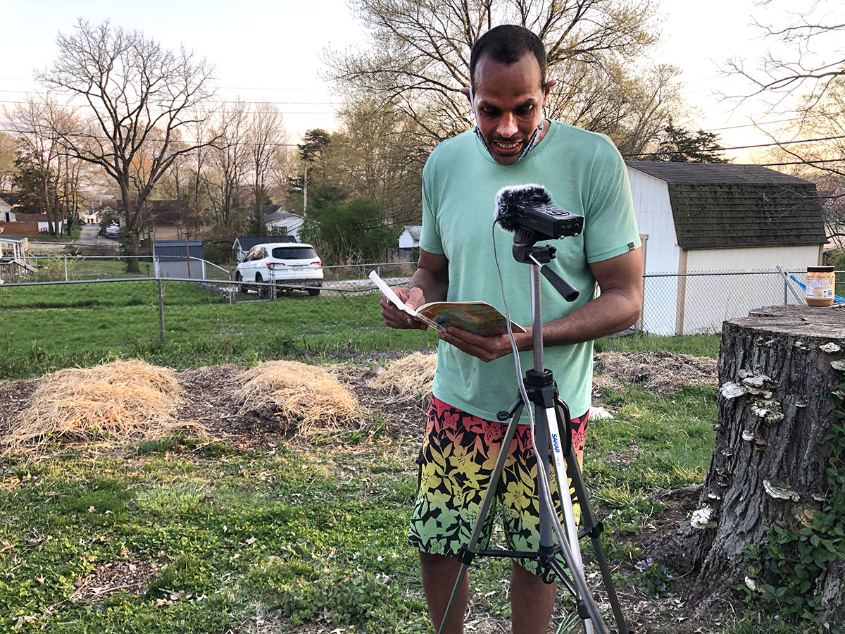 Ross Gay in t-shirt and shorts reading from a book in an early spring garden in front of a microphone on a tripod.
