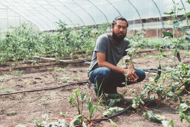 Shane Bernardo crouching in a hoop house, with cucumbers on a vine.