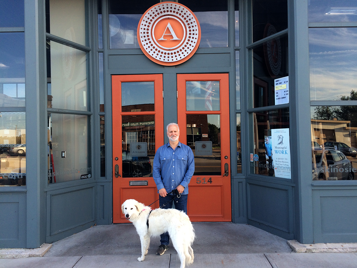 Shawn Askinosie standing in front of a storefront with a large white dog.