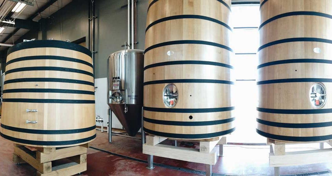 Three tall wooden vats in a large room