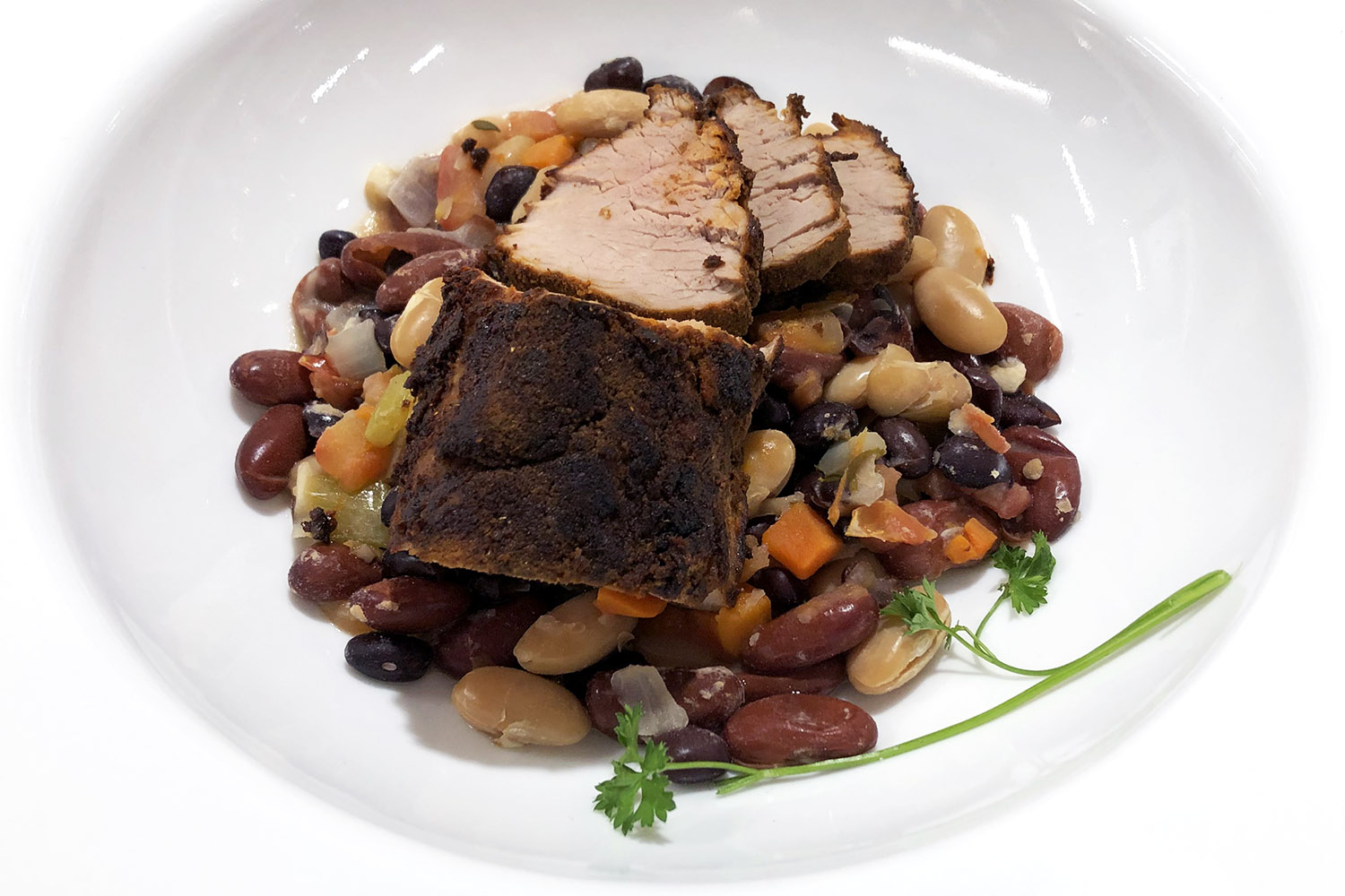 Slices of roasted meat on a bed of different types of beans.