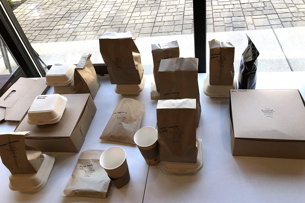 A table with closed paper bags, paper coffe cups, cardboard boxes and clamshell containers.