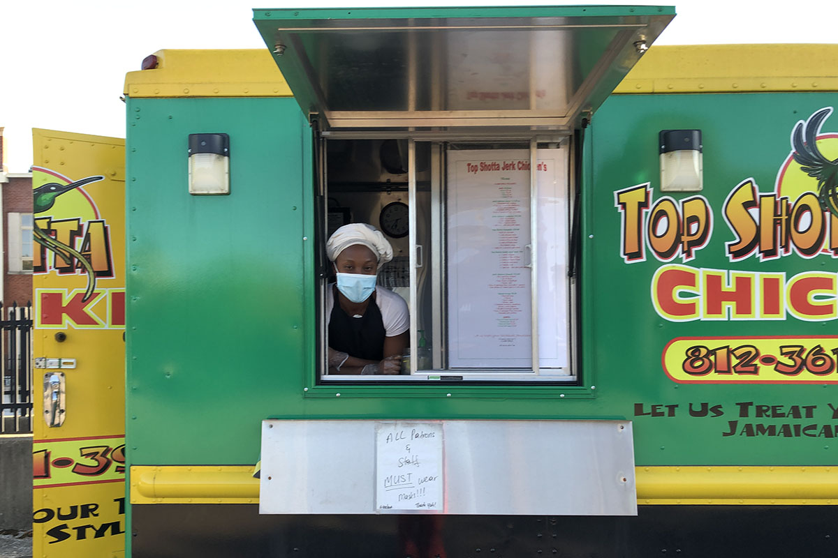 Taneisha Henline with face mask and scarf around hair, in window of yellow and green food truck