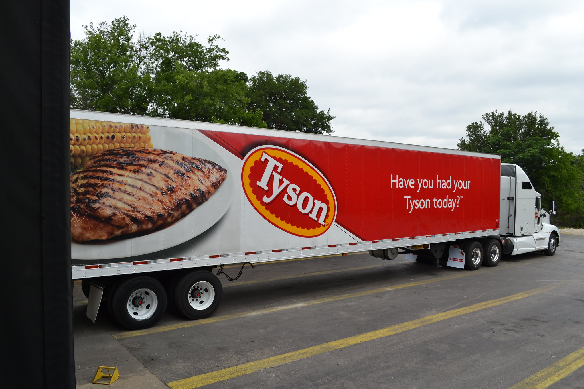 A semi-truck on a road with an image of a plate of food, the Tyson logo and 'Have you had your Tyson today?'