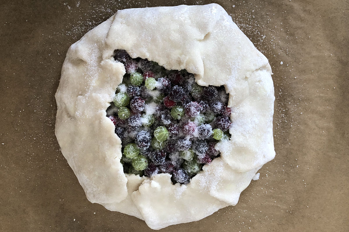 Roughly round-shaped unbaked pie pastry with berries inside.