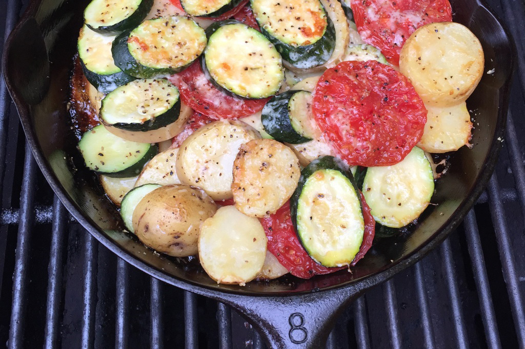 Potatoes, tomatoes and zucchini sliced in rounds, arranged in a cast iron skillet on a grill.