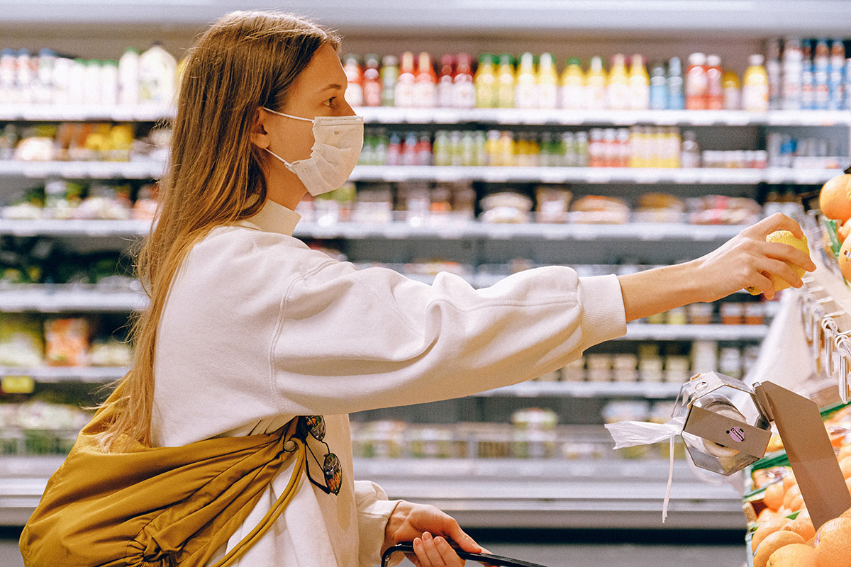 Profile view of a young white woman with a surgical mask and a cloth backpack, reaching fro an orange on a shelf in a grocery store.