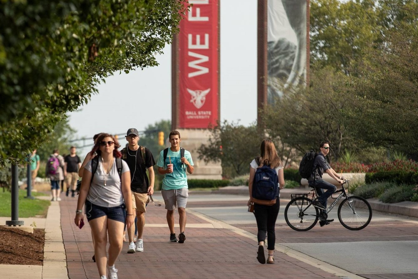 Students walk outside on a warm day at the Ball State University campus.