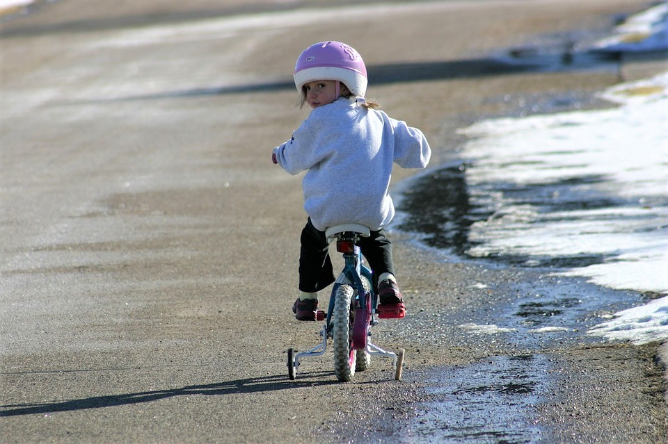 A stock image of a child wearing a helmet while riding a bicycle with training wheels.