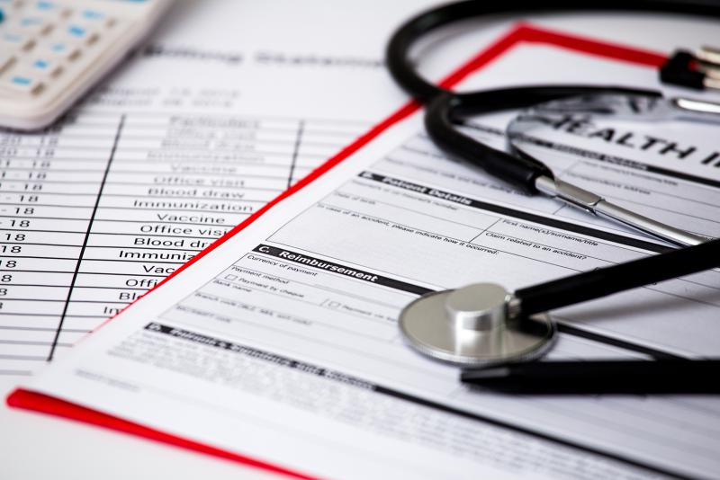 A stock image of healthcare and insurance-related documents under a stethoscope.