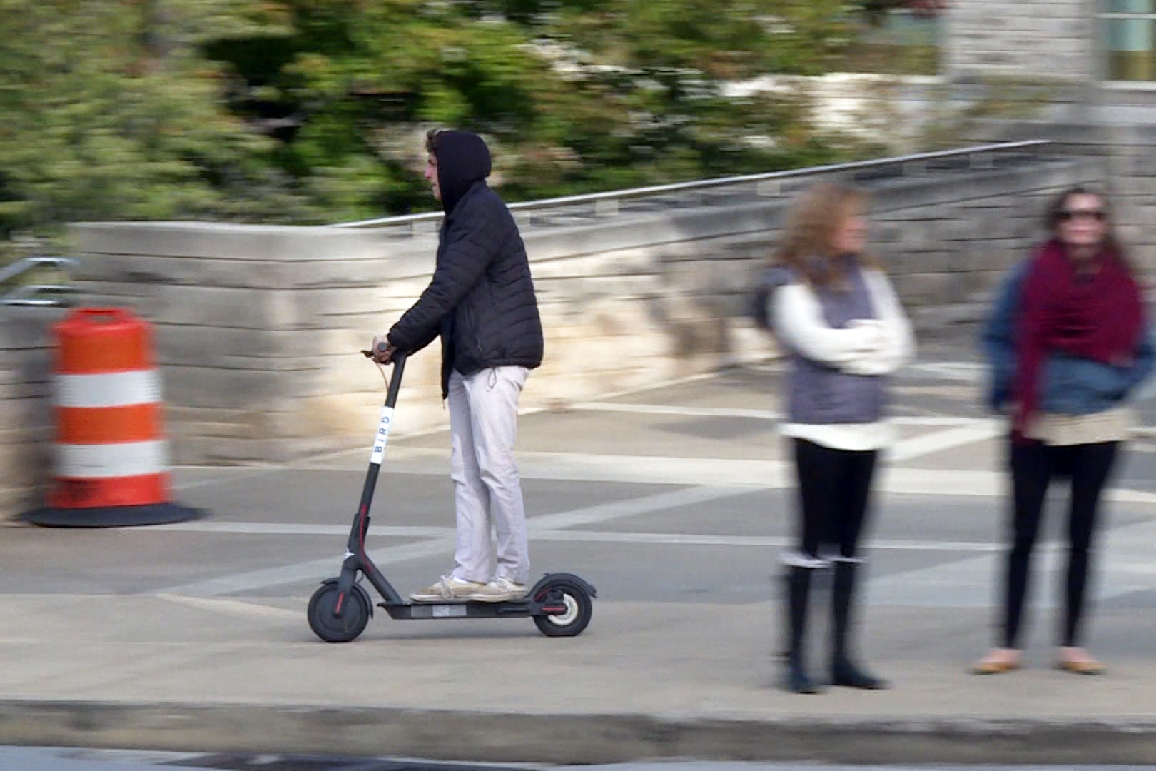 A student rides a Bird electric scooter through campus.