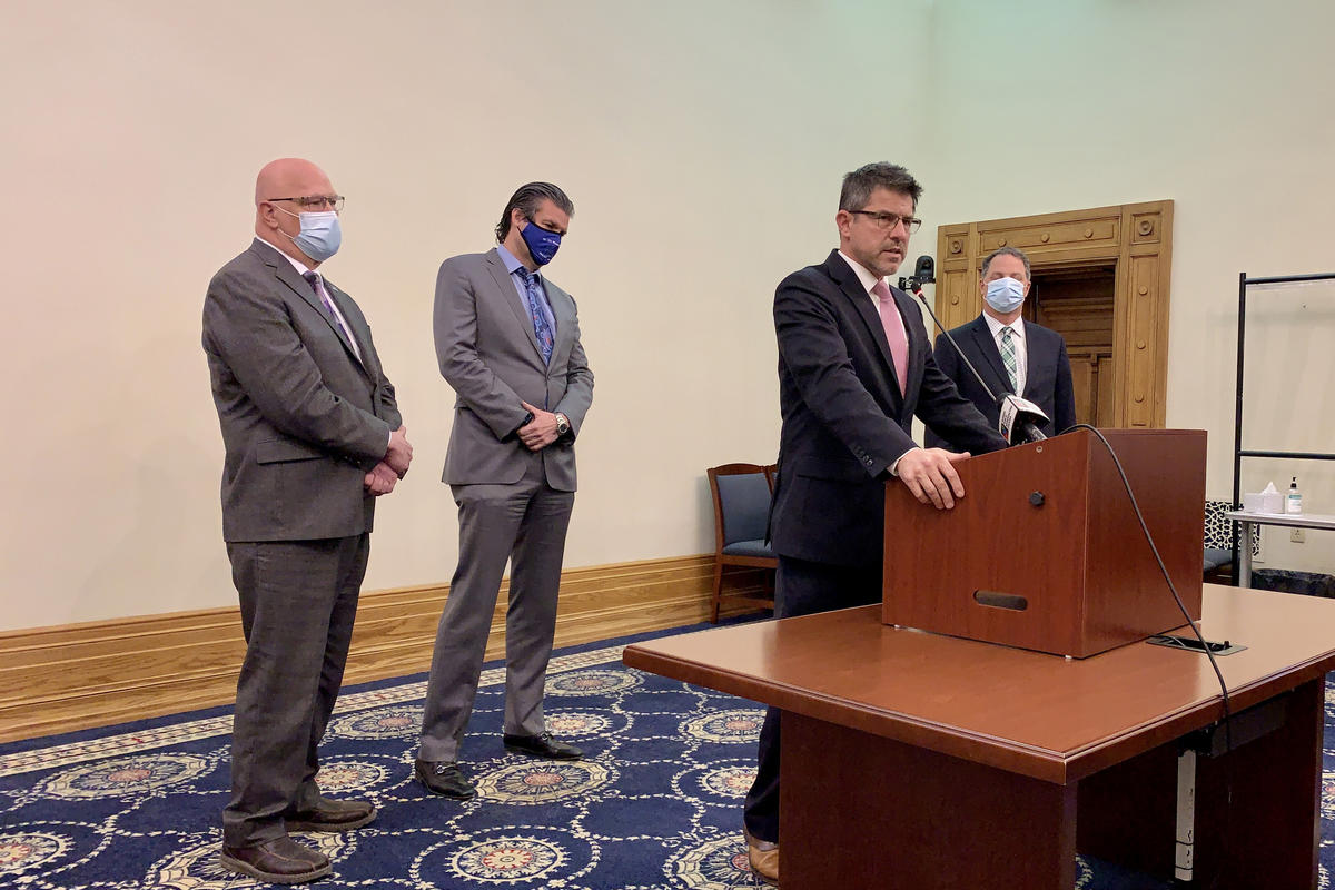 Senate President Pro Tem Rodric Bray (R-Martinsville) speaks at a lectern about the latest revenue forecast. Behind him, from left, Rep. Tim Brown (R-Crawfordsville), Sen. Ryan Mishler (R-Bremen) and House Speaker Todd Huston (R-Fishers)