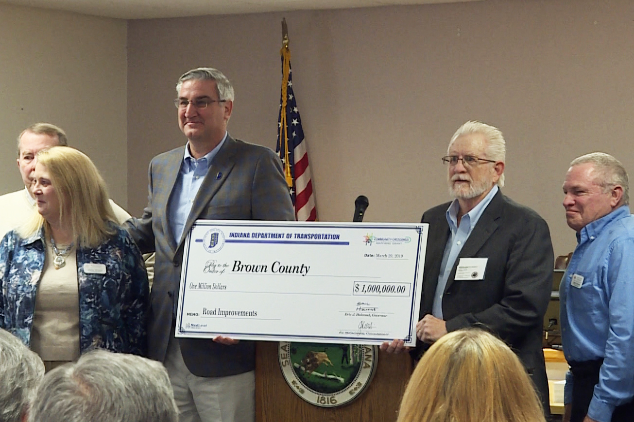 Gov. Eric Holcomb stands with a large check for $1 million made out to brown county