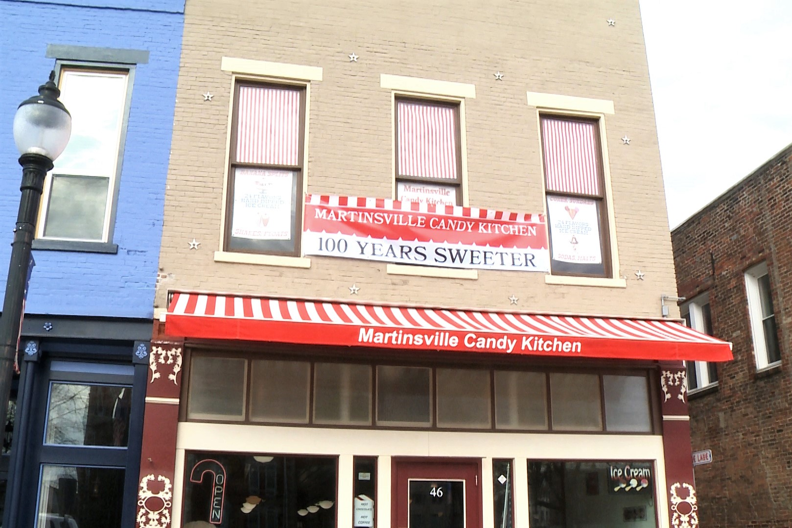 "Exterior of Candy Kitchen with ""100 Years Sweeter"" banner"