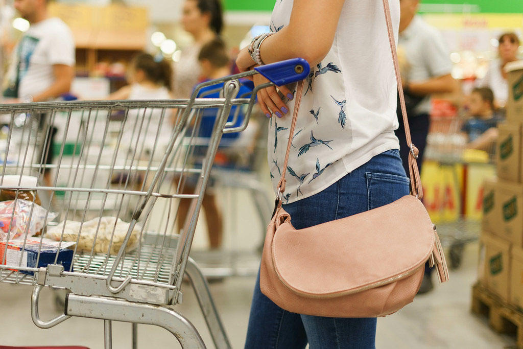 Stock image of a woman's torso and a shopping cart.