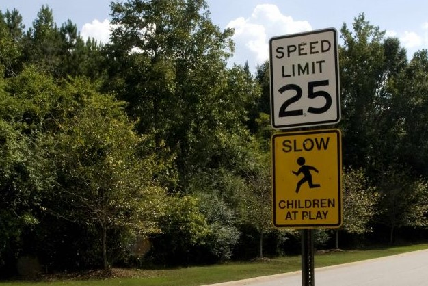 "A 25-mph speed limit sign above a sign reading ""slow -- children at play."""