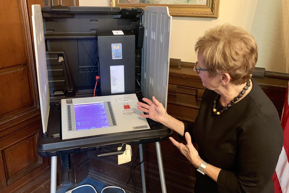 Secretary of State Connie Lawson demonstrates the use of a paper audit trail on an electronic voting machine.