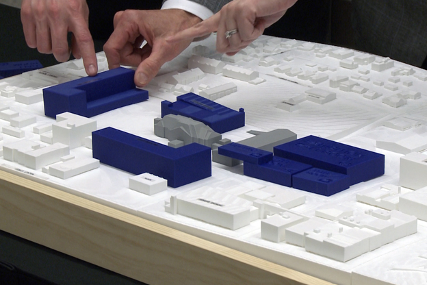 residents point to a 3-D model of the convention space