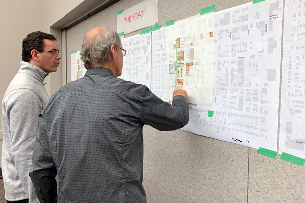 Residents look at wall sketches
