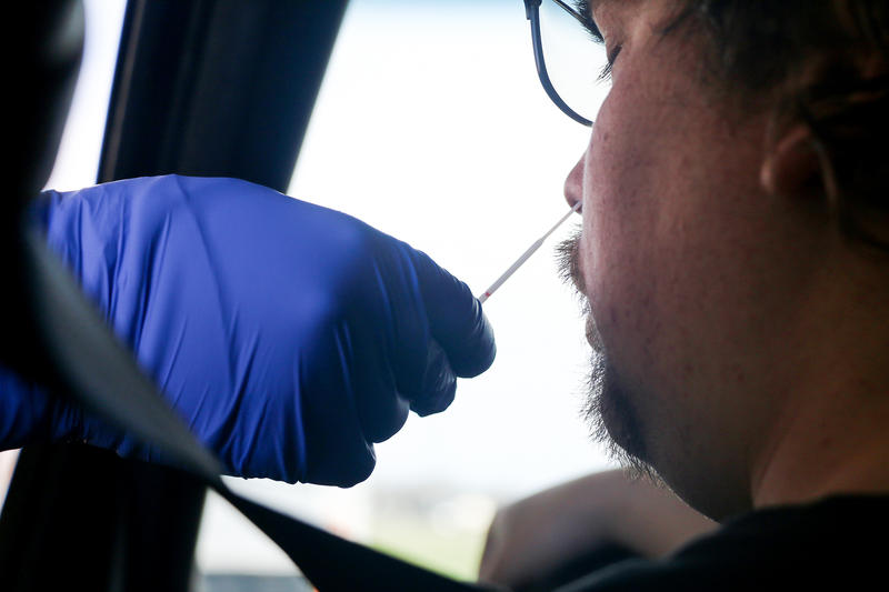 A person receiving a nasal swab test for COVID-19 or coronavirus in their car.