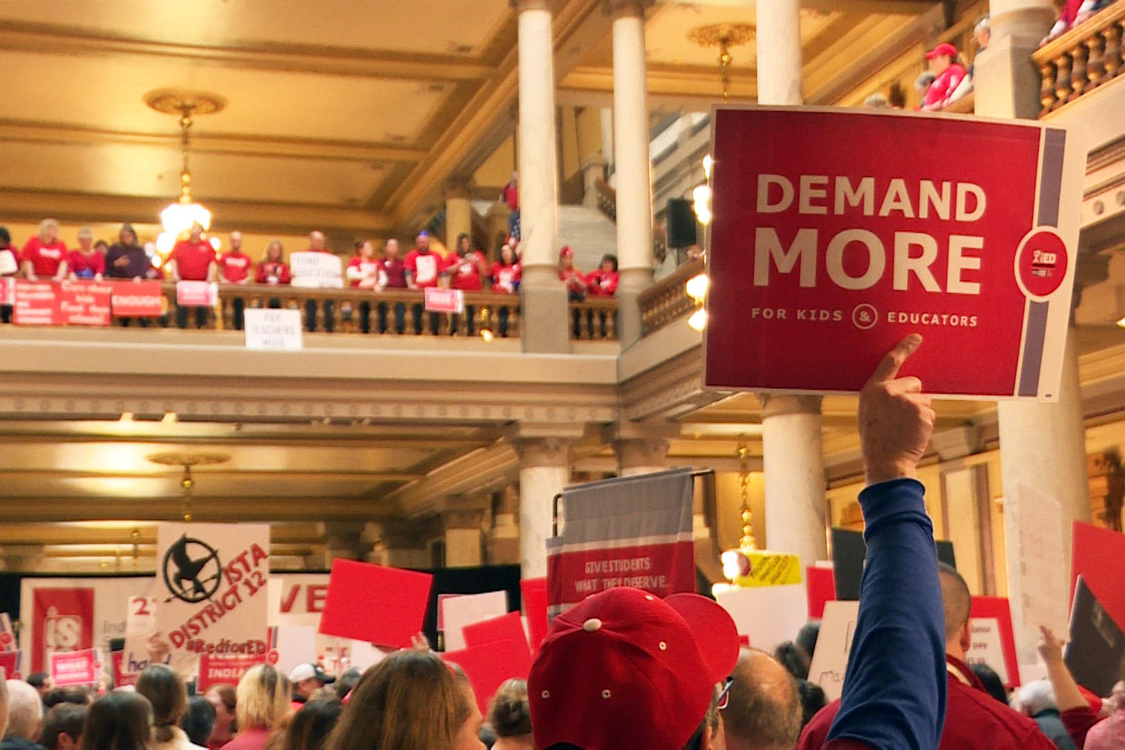 A man holds a red Demand More sign above a crowd at the Indiana Statehouse