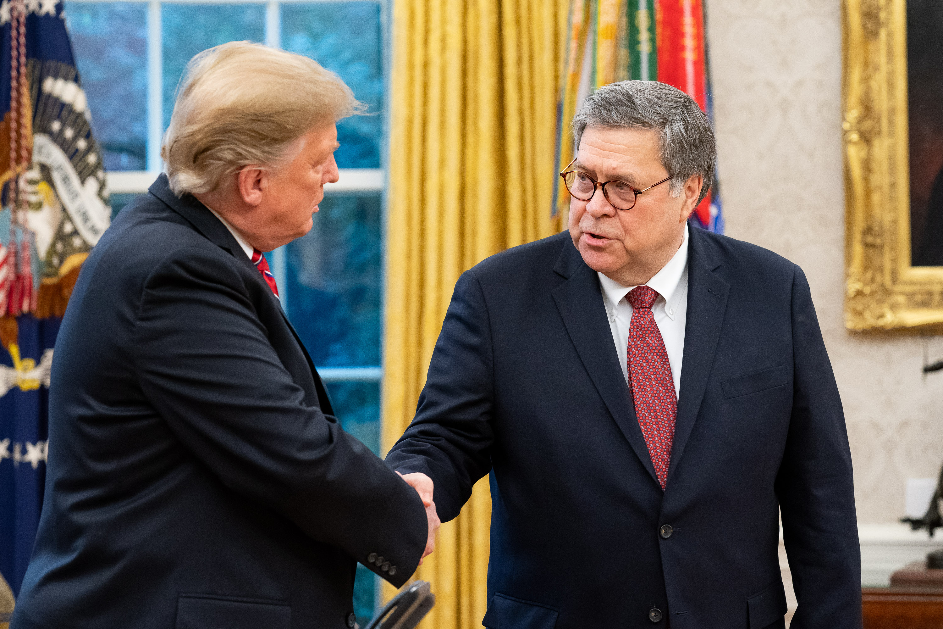 President Donald Trump and U.S. Attorney General William Barr shake hands in the Oval Office.