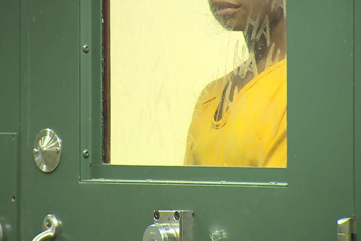 An inmate at the Evansville Jail looks through a cell door.