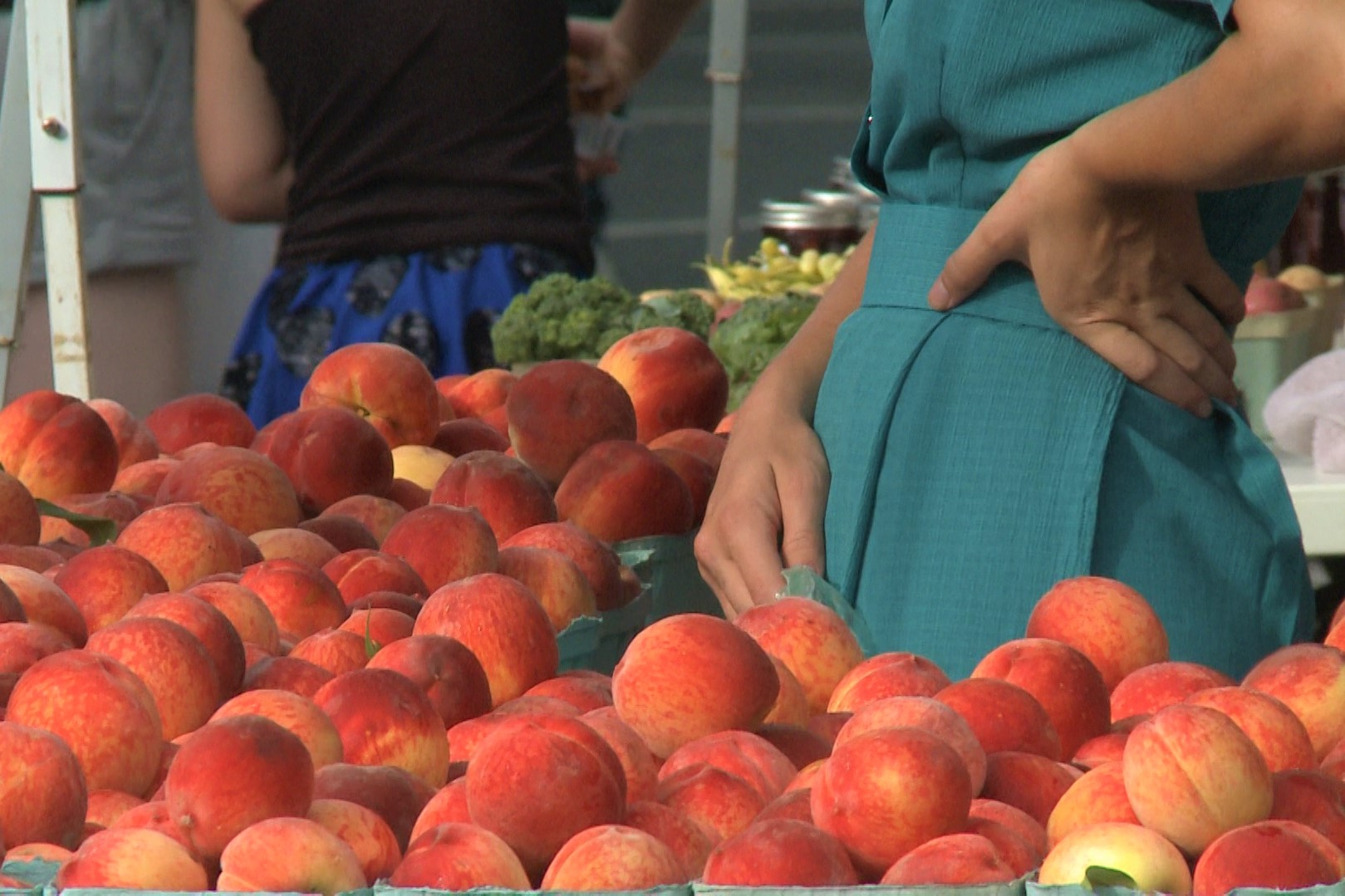 A vendor stands by her peaches at the Farmers' Market. Summer 2019.